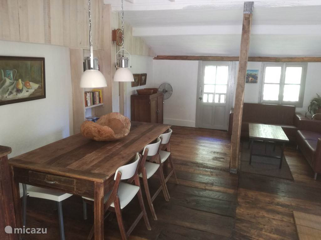 De huiskamer met zicht op het zitgedeelte en de deur naar het balkon.