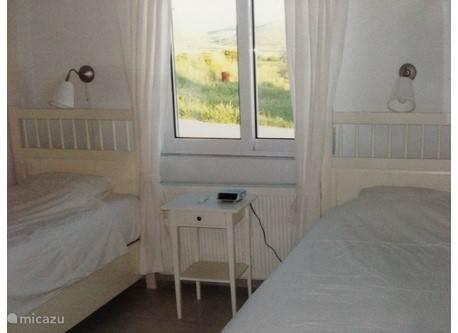 Slaapkamer met 2 1-persoonsbedden, airconditioning en een ruime muurkast.