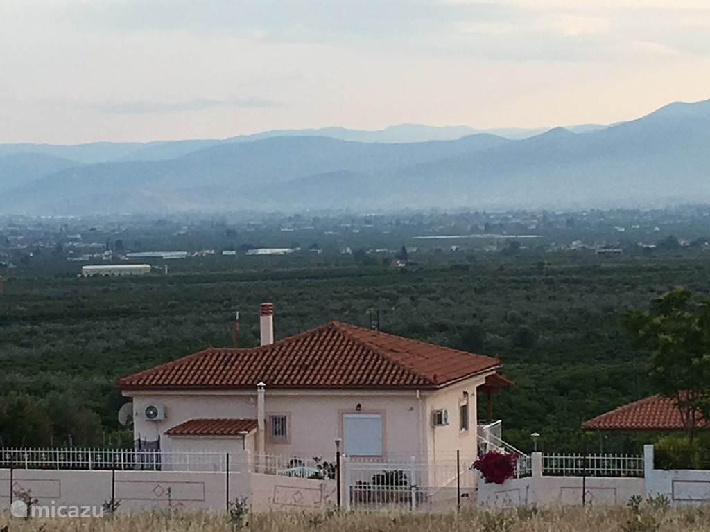 Uitzicht vanaf het huis op de aangrenzende citrus en olijfboomgaarden, de bergen en de zee.