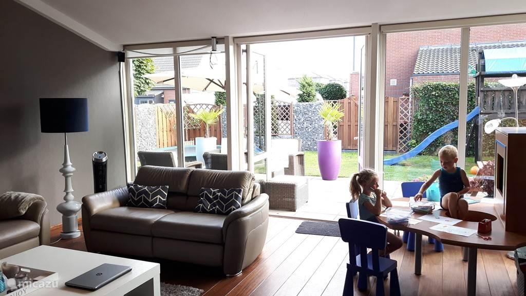 luxe zithoek met relaxfauteuils en openslaande deuren naar de open tuin. Tevens ruime speelhoek voor de kinderen