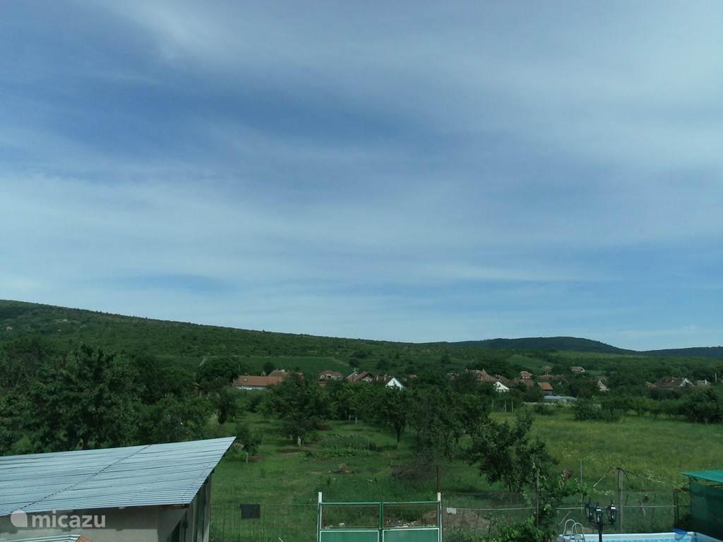 Het uitzicht wat er is op de bergen en boomgaard.