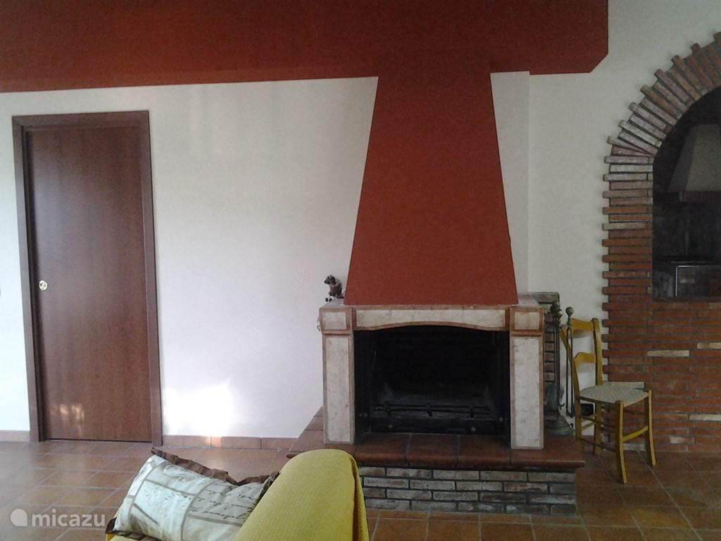 Openhaard in woonkamer met links toegang tot slaapkamer.