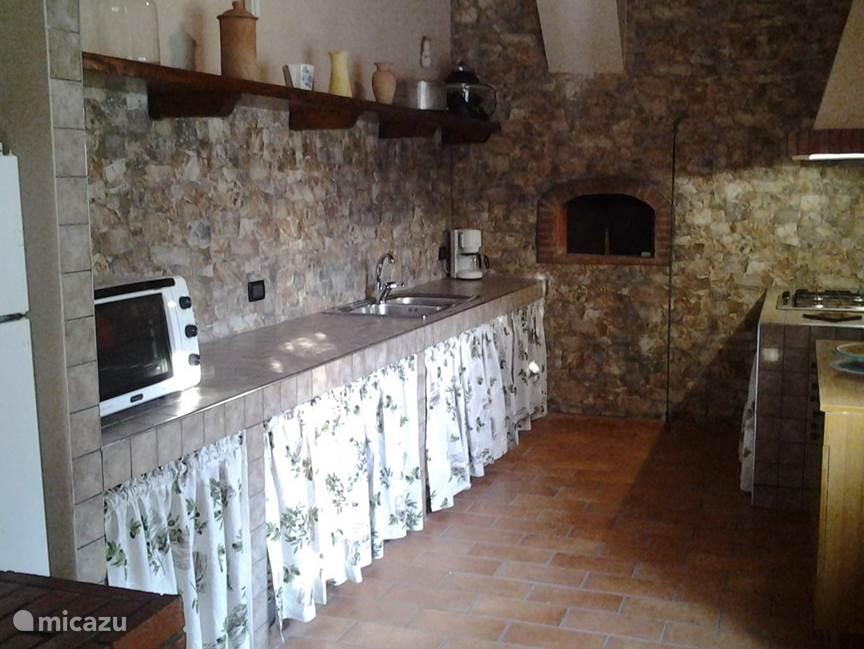 Keuken met pizza oven op achtergrond.
