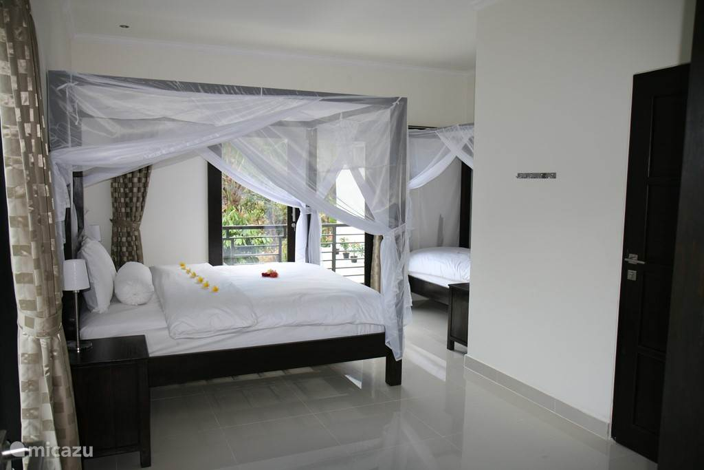Spacious bedroom with sliding doors to the balcony and indoor bathroom.