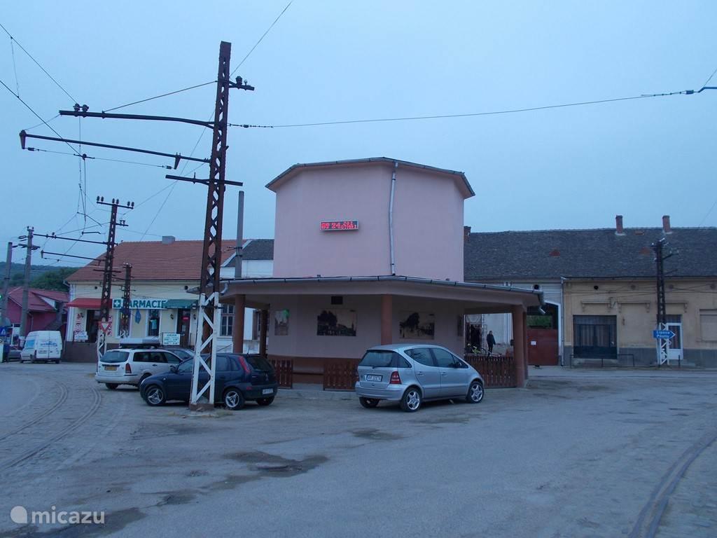 In het dorps centrum met op het gebouw foto's van rond 1900