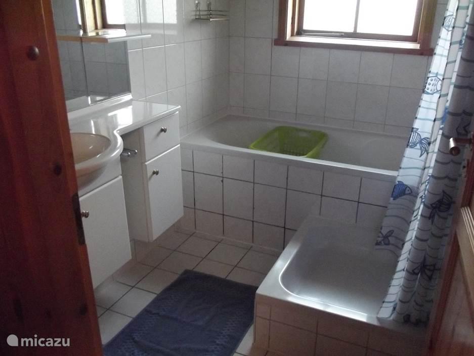 De badkamer met zowel bad als douche