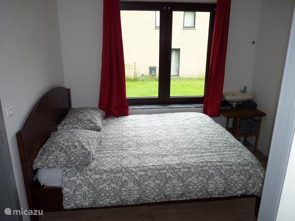 Slaapkamer met royaal bed en wastafel, badkamer en suite.