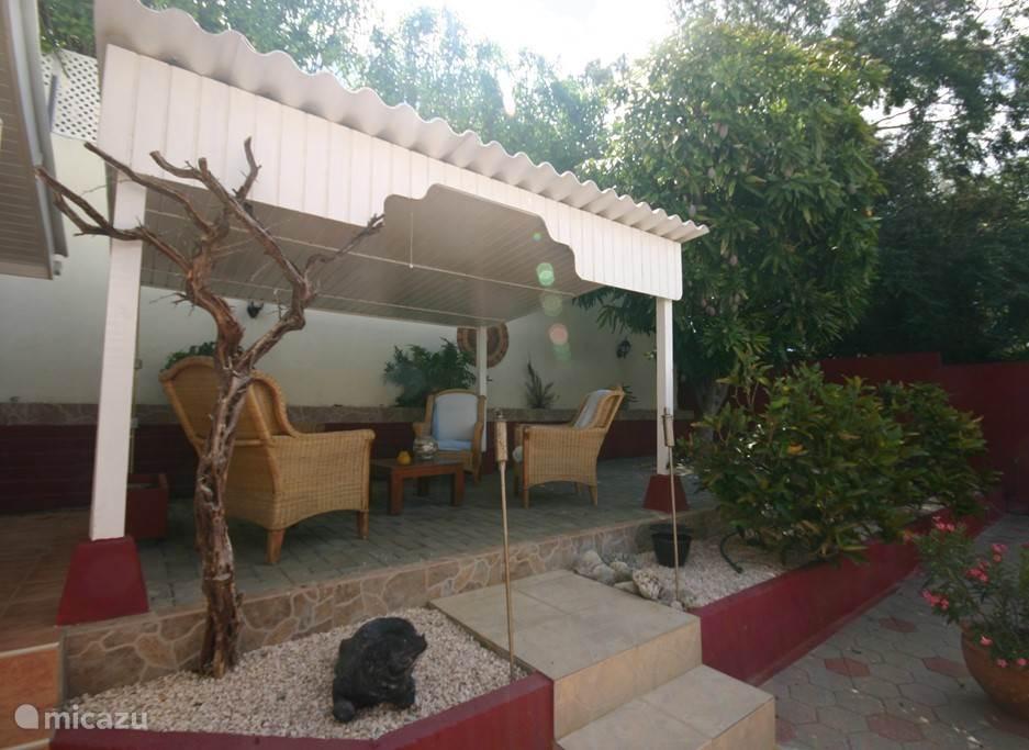 Privé tuin met overdekt terras en Mangoboom.