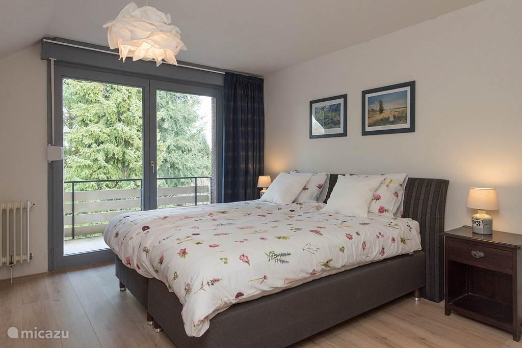Master bedroom heeft een boxspring van 180 bij 200 cm. met balkon en uitzicht op de tuin.