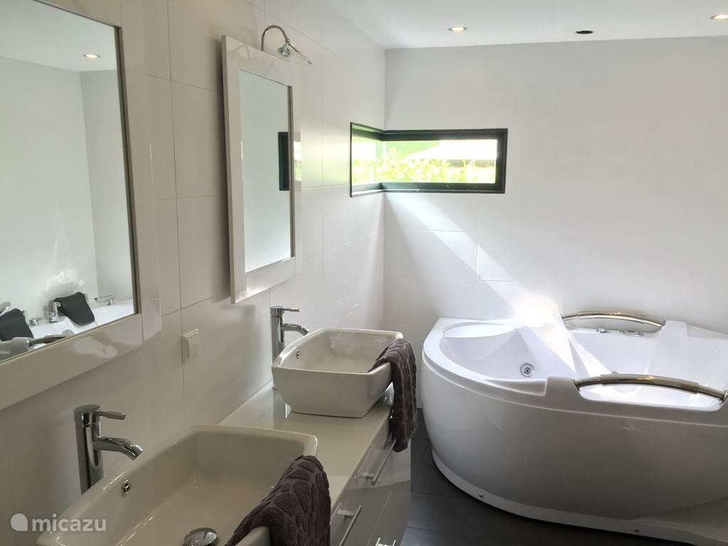 In de luxe badkamer bevind zich de twee persoons whirlpool, dubbele wastafel en ruime inloop regendouche.