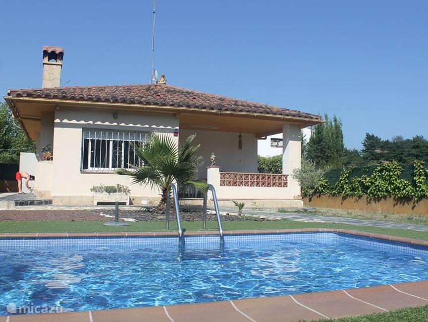 Voorkant van het huis, zwembad en tuin.