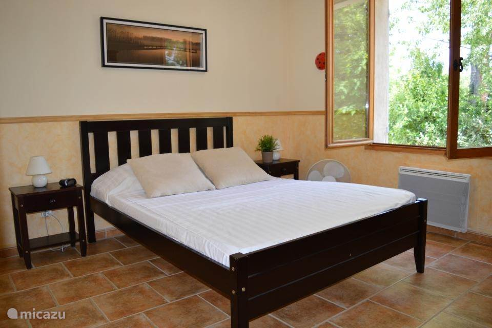 Slaapkamer met een tweepersoonsbed en kleding kast. Gelegen aan de achterkant van het huis.