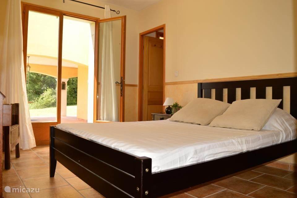 Slaapkamer met een tweepersoonsbed en kleding kast. Gelegen aan de achterkant van het huis met toegang tot de binnentuin.