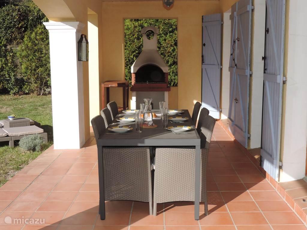 Ruim overdekt terras met recent nieuw aangeschafte tafel + 6 stoelen, waar u lekker aan kunt eten en eventueel gebruik kunt maken van de grote barbecue.