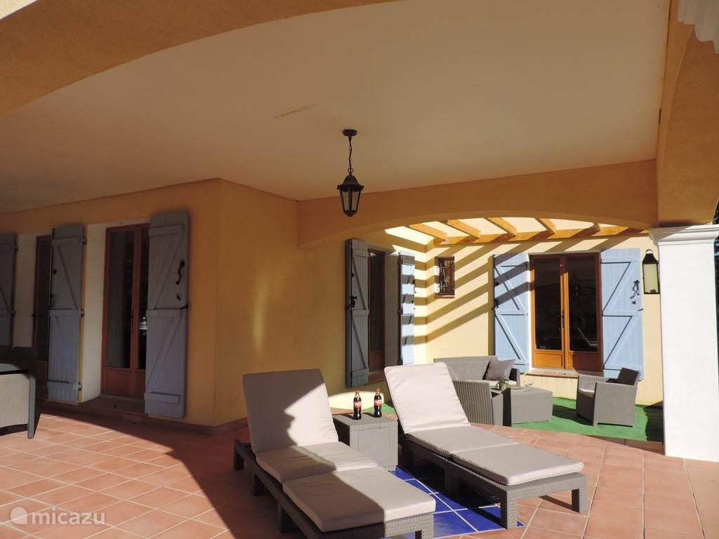 Groot overdekt terras waar u bijvoorbeeld de ligbedden kunt neer zetten ook het loungeset staat hier erg goed.
