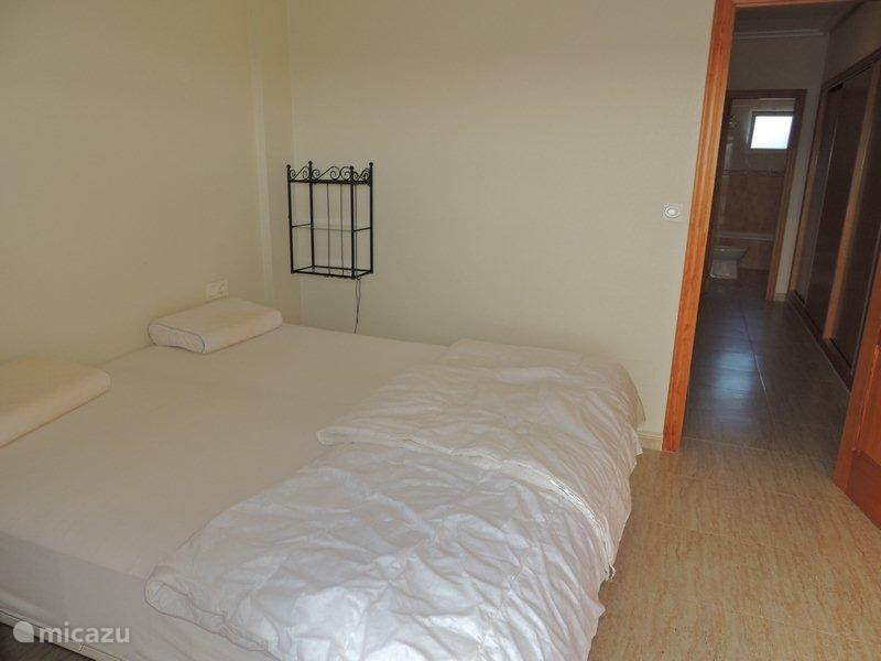 slaapkamer met dubbel bed en terras