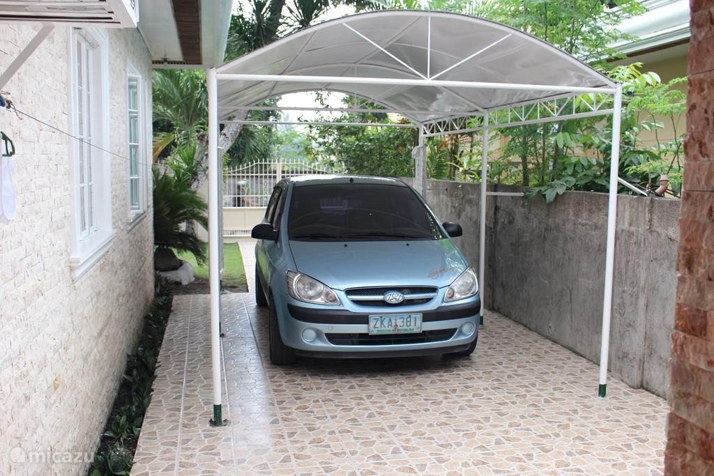Zijkant huis met carport. Auto (Hyundai Getz) is optioneel te huur.