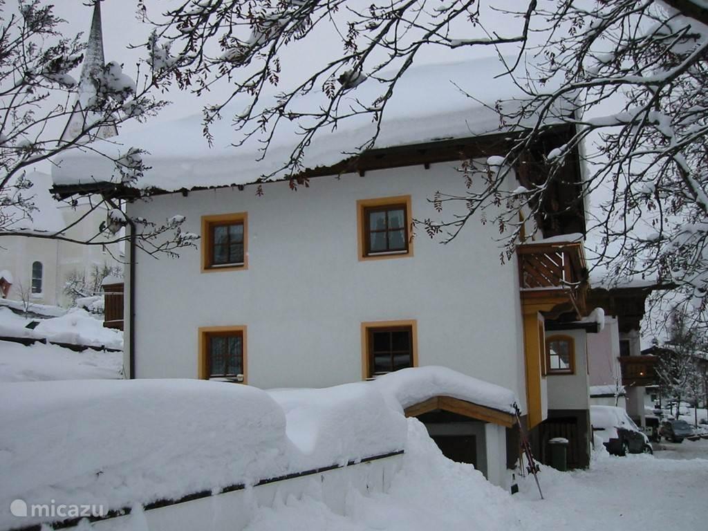 Zijkant van de woning met op de achtergrond de kerk. Na het skiën via de kelder naar binnen waar een ruime kelder met ruime opslag.