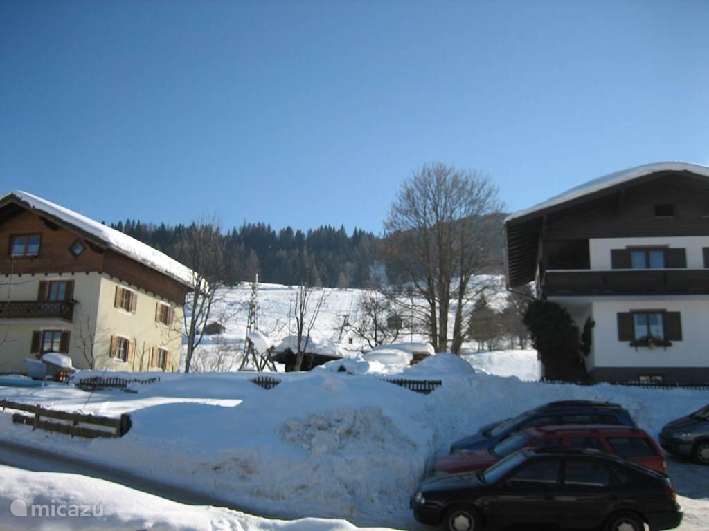 Zicht vanuit de woonkamer op de piste en skilift