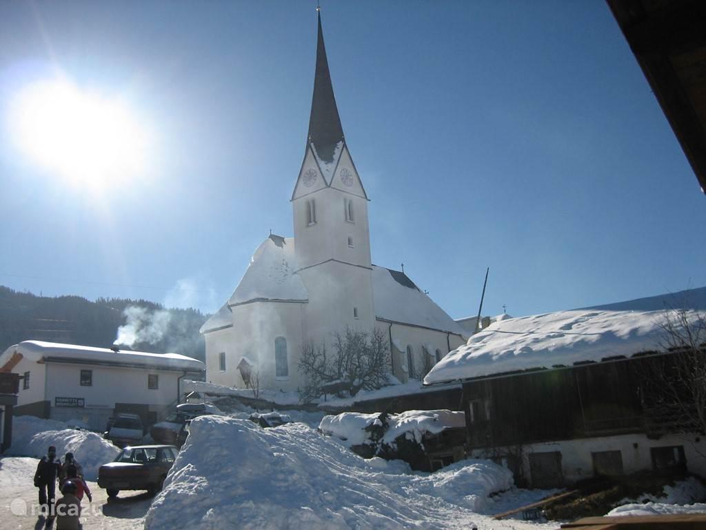 Zicht op de kerk en de Horndl Hutte onder aan de piste.