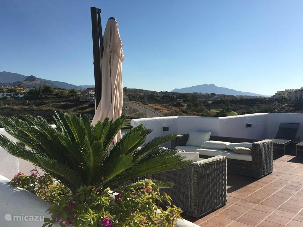 Dit terras heeft een loungehoek, 4 ligbedden en een barbequehoek.