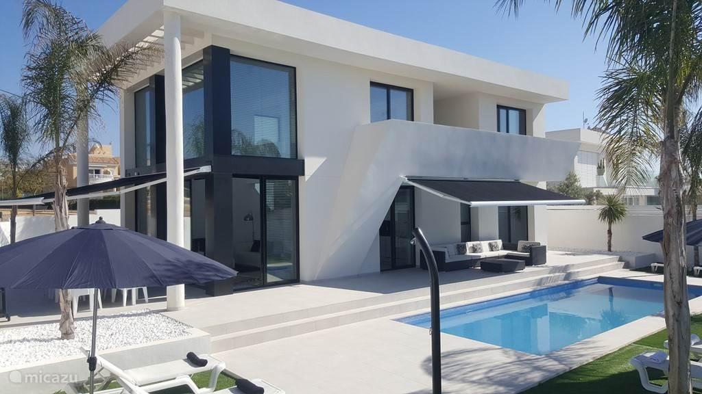 achterzijde van de woning met grote tuin en zonneterras en groot zwembad