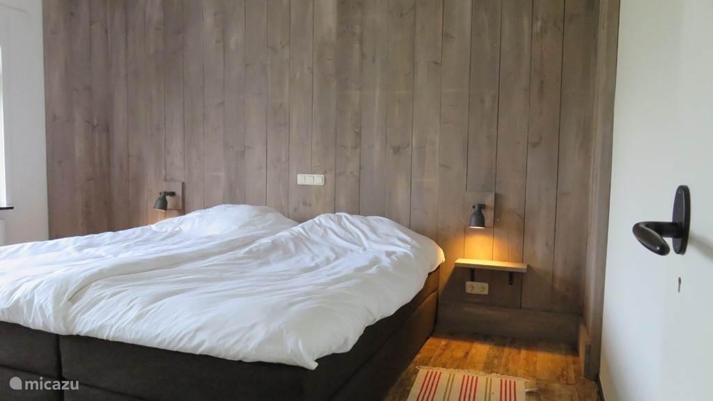 Masterbedroom. Gelegen op de begane grond aan de achterzijde van de woning. Royale luxe hotelboxspring met een bedmaat van 2.00 x 2.10 meter. Vanuit deze rustig gelegen slaapkamer kun je met het raam open de schepen op weg naar Vlissingen en Antwerpen horen toeteren.