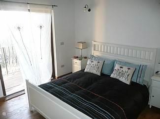 1e slaapkamer met 2 persoonsbed en openslaande deuren naar balkon