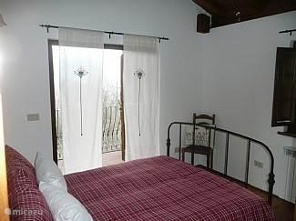 2e slaapkamer met 2 persoonsbed met openslaande deuren naar balkon