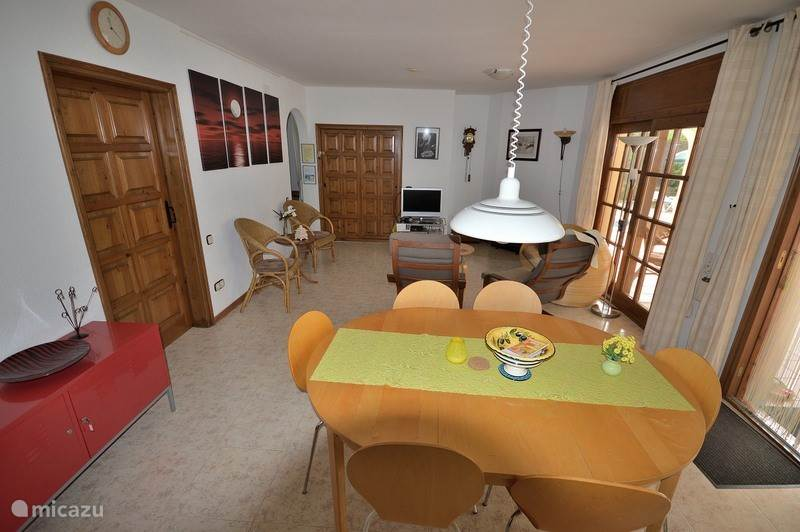 Huiskamer met Nederlandse tv en toegang tot terras met zwembad en buiten BBQ.
