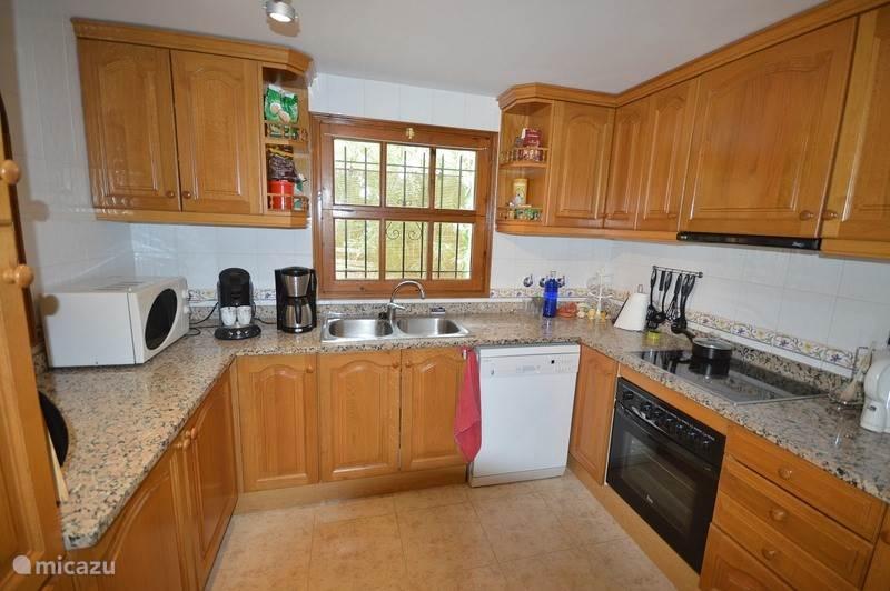 Keuken met vaatwasser, koffiezet apparaat, waterkoker, broodrooster, magnetron, oven en keramische kookplaat.
