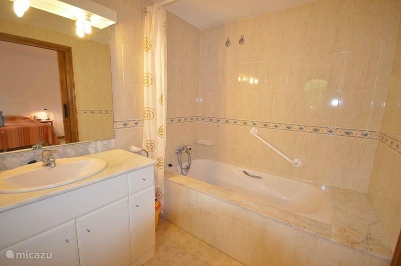 Badkamer direct aan slaapkamer beneden. Douche, bad en toilet, allen met stevige handvaten, speciaal voor mindervaliden.