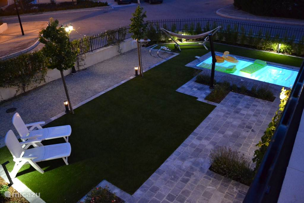 Photo of the garden at night, taken from the roof terrace.