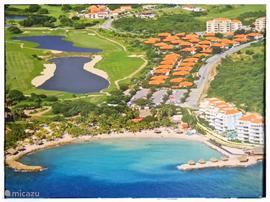 Overzicht van Blue Bay Village met zicht op de golfbaan en het strand.