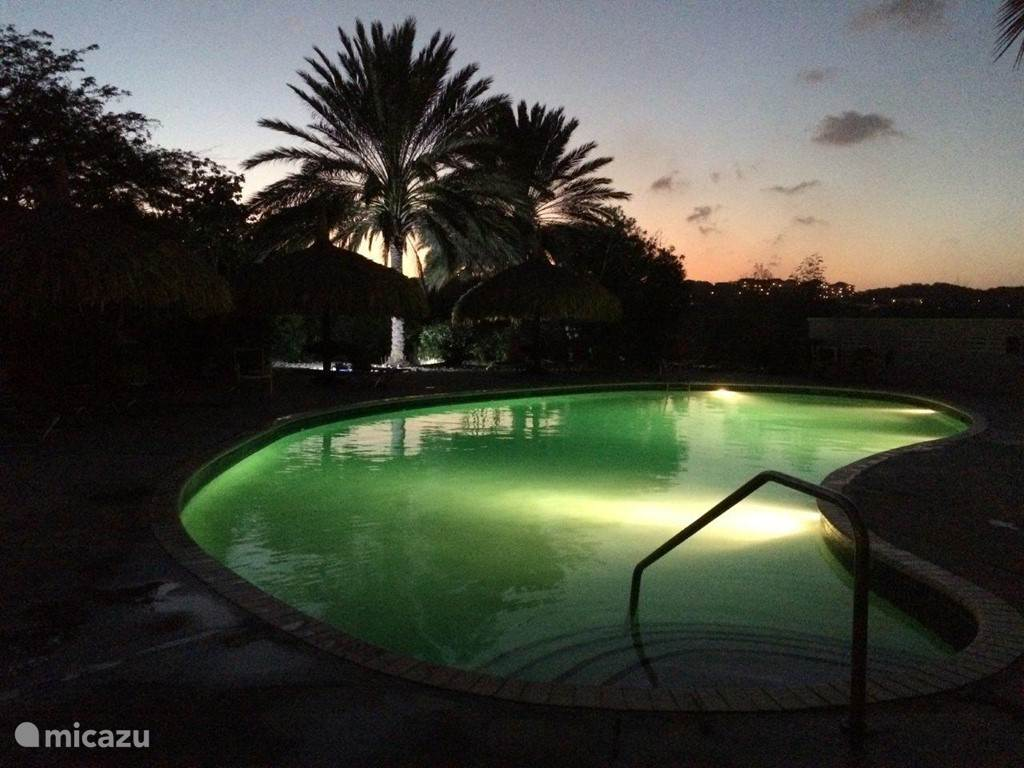 Nicely lit pool at night diagonally to our villa