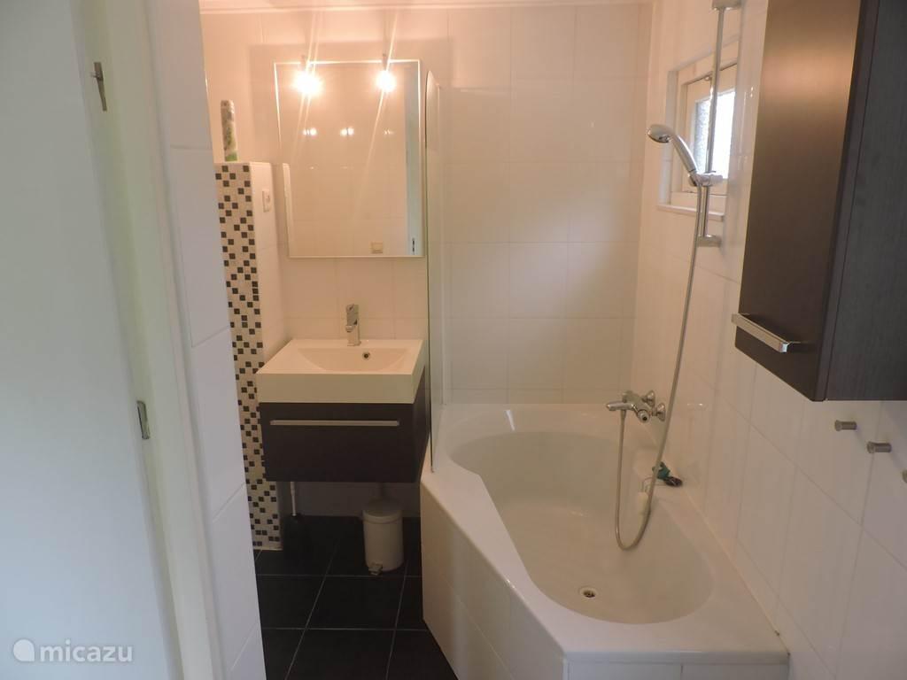 Een ligbad is aanwezig. De badkamer heeft ook een droogrek en enkele kledinghaakjes.