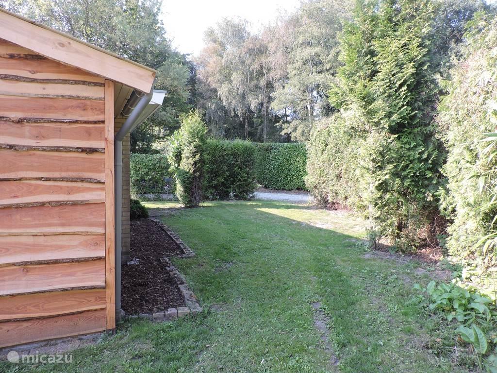 Het huisje heeft een ruimte tuin rondom met veel privacy.