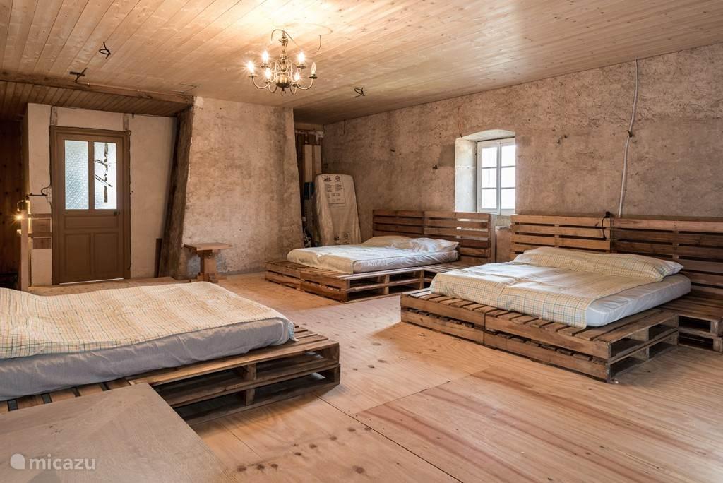 Slaapzaal met drie tweepersoonsbedden, overal stopcontacten en kleine verlichting om te lezen zonder anderen te storen.