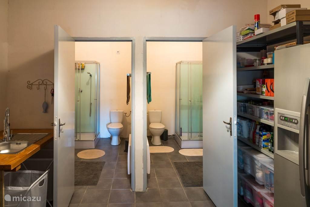 Zicht op twee douchecellen vanuit de bijkeuken