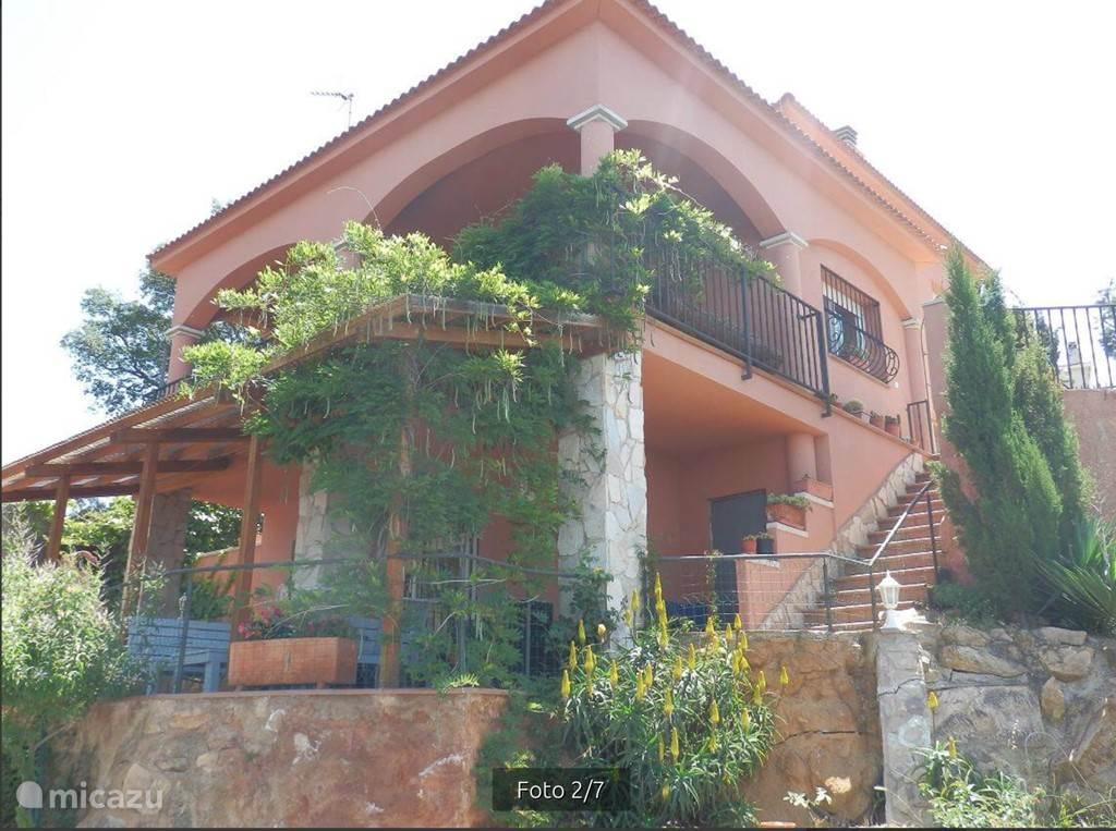 Het huis vanaf het terras bij het zwembad.