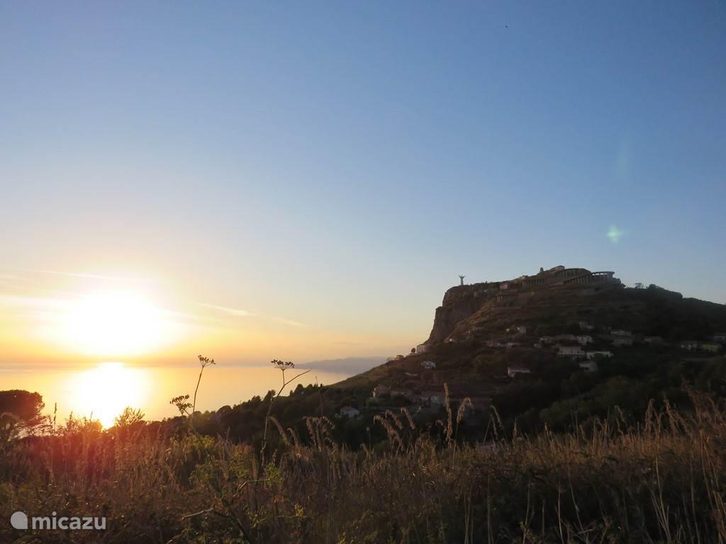 Christusbeeld en Monte San Biagio bij zonsondergang