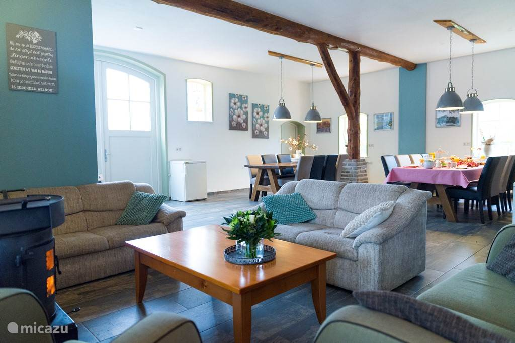 Sfeervolle woon/eetkamer met open keuken en loungehoek met houtkachel.