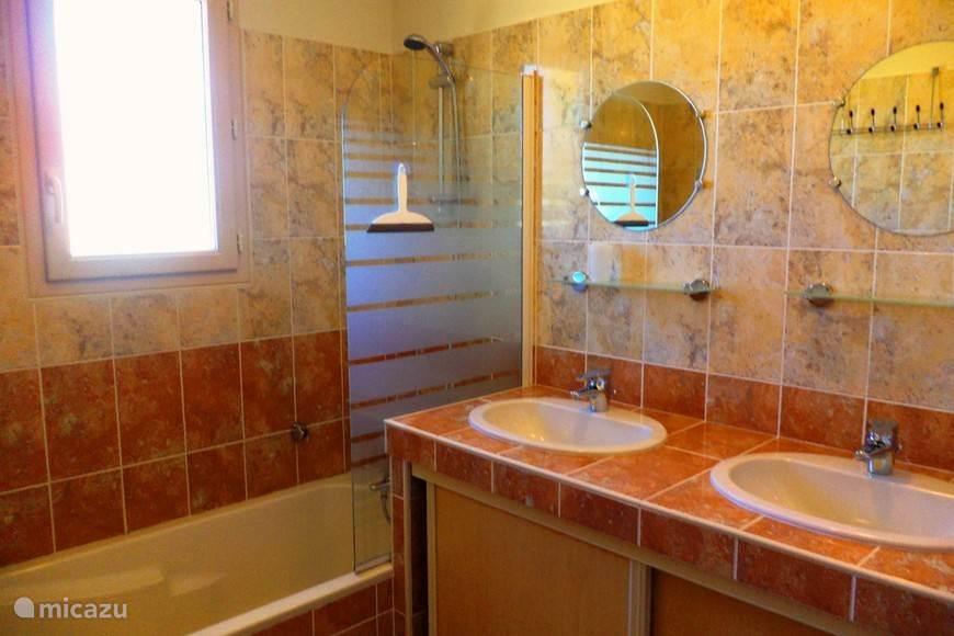 Badkamer met wastafels en bad/douche
