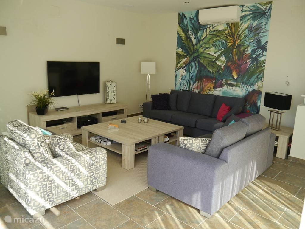 Woonkamer met comfortabele banken en 55 4K TV met surround set.