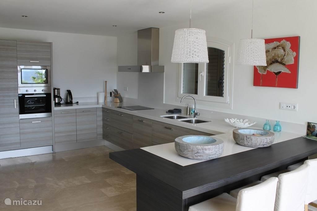 Beneden bevinden zich de zeer ruime woon/eetkamer, een half open leef keuken met eetbar en een apart toilet. De woonkamer en keuken grenzen beiden aan het luxe terras met zwembad.