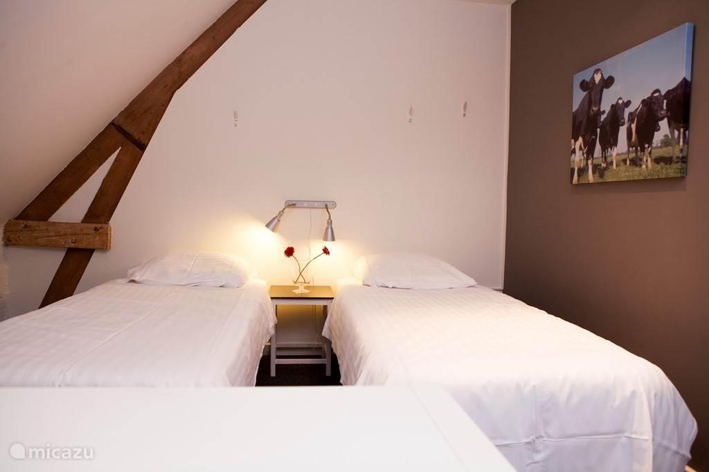 slaapkamers boven met 4 boxspringbedden , dekbed en kussen.