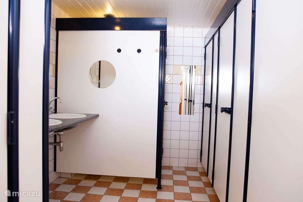 sanitaire ruimte met 3 douchescabines, 3 wastafels en 3 toiletten  en vloerverwarming.