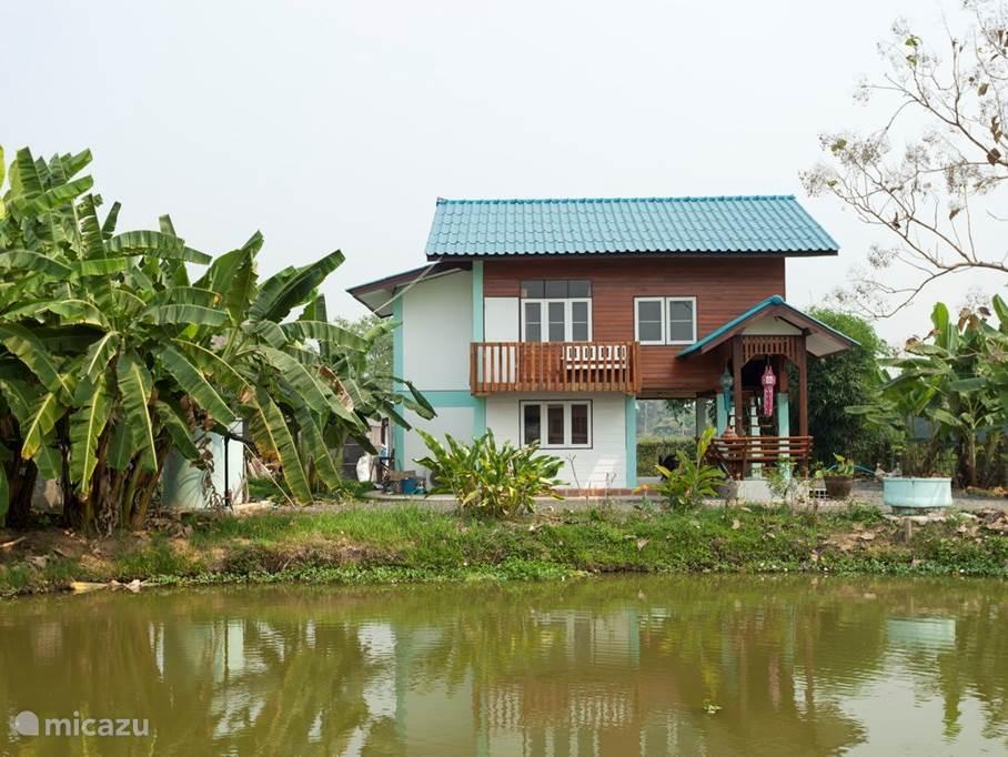Teakhouten huis gezien over de visvijver
