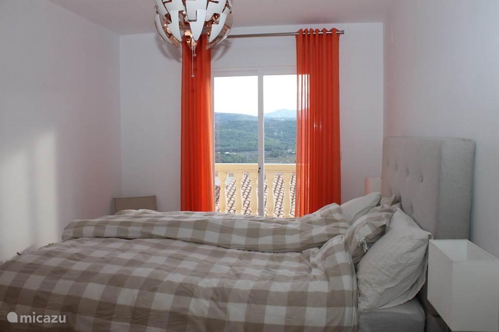 slaapkamer beneden met tweepersoonsbed en balkon