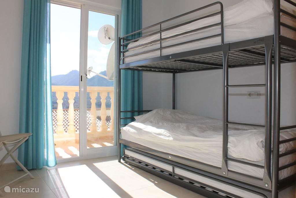 slaapkamer beneden met stapelbed en balkon